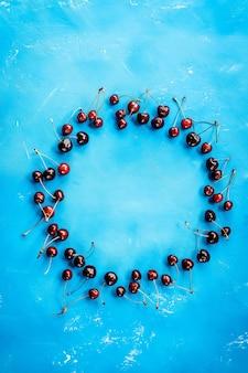 Deliciosas cerezas rojas maduras en la pared azul dispuestas en el marco del círculo. creativa maqueta de alimentos cuadrados con espacio de copia para el diseño. vista superior. endecha plana. círculo de frutas. cerezas maduras