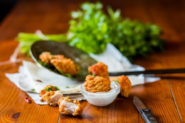 Deliciosas croquetas de pollo crujiente con salsa de ajo en la mesa de madera