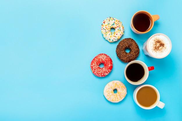 Deliciosas donas y tazas con bebidas calientes, café, capuchino, té sobre una superficie azul. c