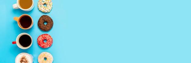 Deliciosas donas y tazas con bebidas calientes, café, capuchino, té sobre una superficie azul. concepto de dulces, panadería, pastelería, cafetería, reunión, amigos, equipo amigable. vista plana, vista superior