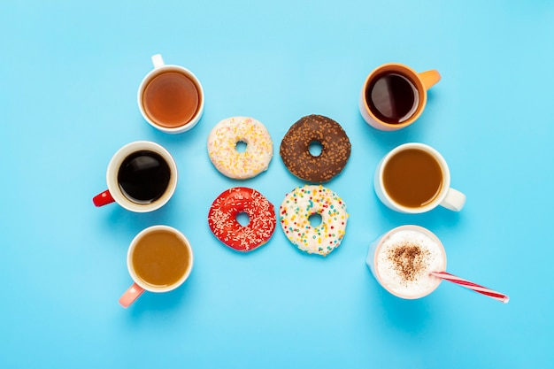 Deliciosas donas y tazas con bebidas calientes en una superficie azul. concepto de dulces, panadería, pastelería, cafetería, amigos, equipo amigable. vista plana, vista superior