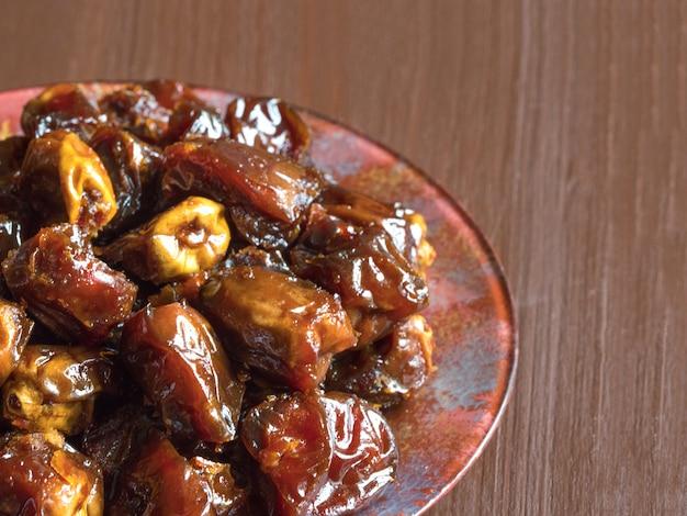 Deliciosas fechas dulces orgánicas en un tazón con jarabe. fechas de iftar.