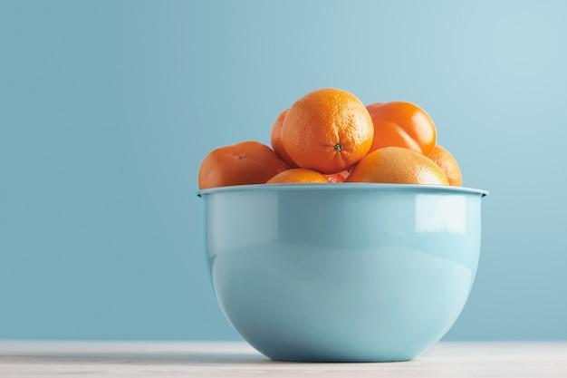 Deliciosas frutas frescas maduras y cítricos en un recipiente azul metálico aislado en una mesa blanca sobre fondo azul pastel: caqui, ciruela, mandarina, naranja, pomelo, pomelo