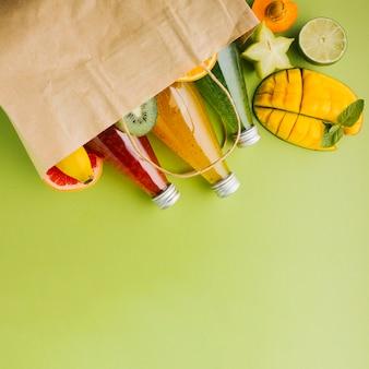 Deliciosas frutas y jugos en bolsa de papel copyspace.