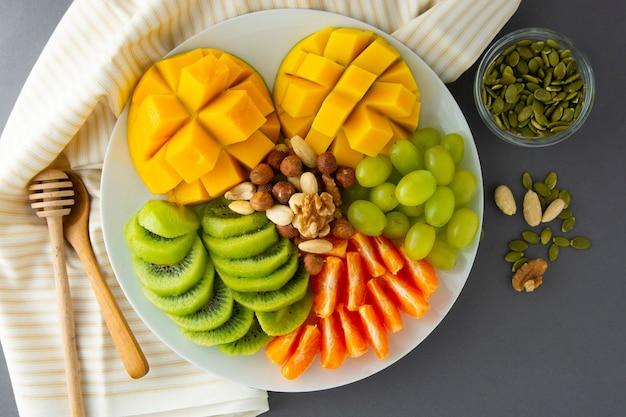 Deliciosas frutas platte con: mango, kiwi, cítricos, nueces, uvas. mezcla de varias frutas exóticas