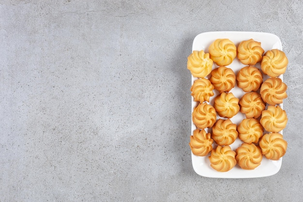 Deliciosas galletas caseras alineadas en un plato sobre fondo de mármol. foto de alta calidad
