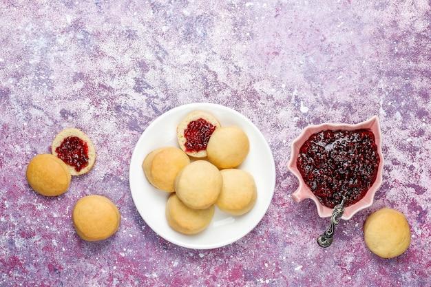Deliciosas galletas caseras que sirven con mermelada de frambuesa, vista superior