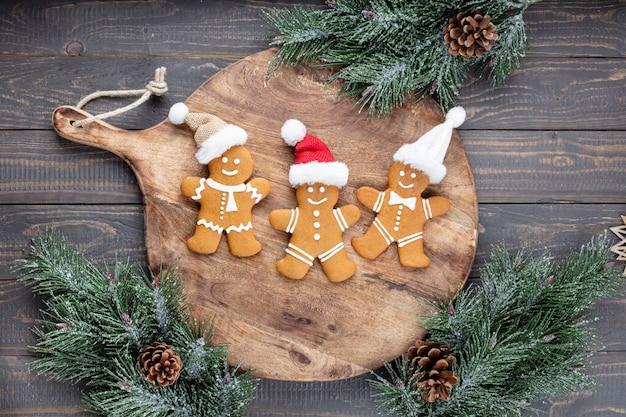 Deliciosas galletas de jengibre y decoración navideña sobre fondo de madera.