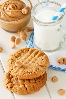 Deliciosas galletas de mantequilla de maní caseras con taza de leche. espacio de madera blanca. merienda saludable o sabroso desayuno concepto.