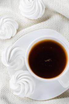 Deliciosas galletas de merengue y una taza de té caliente.
