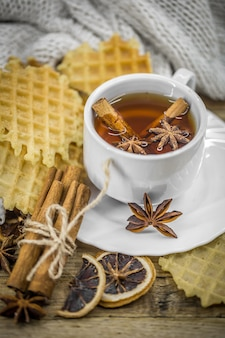 Deliciosas galletas y una taza de té caliente con una rama de canela y una cucharada de azúcar morena sobre madera