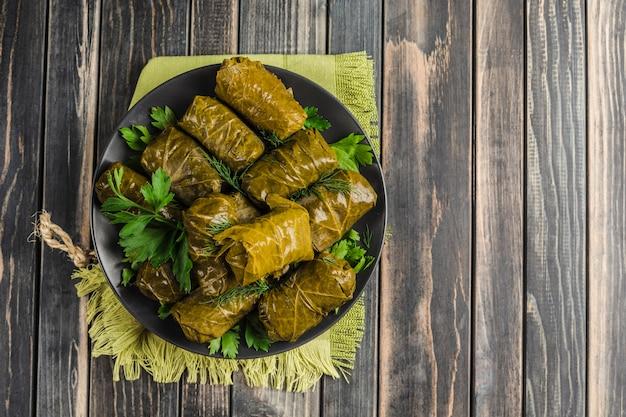 Deliciosas hojas de parra rellenas en un plato negro con cilantro fresco y eneldo