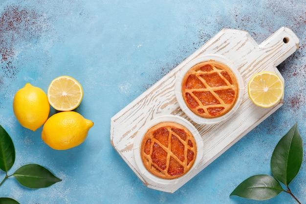 Deliciosas mini tartas de limón con limones frescos, vista superior