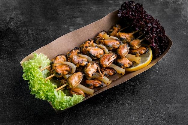 Deliciosas ostras de mariscos en brochetas en un cartón
