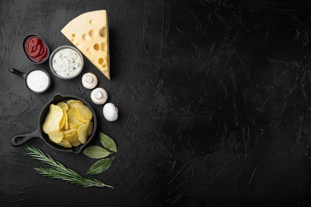 Deliciosas papas fritas crujientes con queso y cebolla, sobre la mesa de piedra negra, vista superior plana