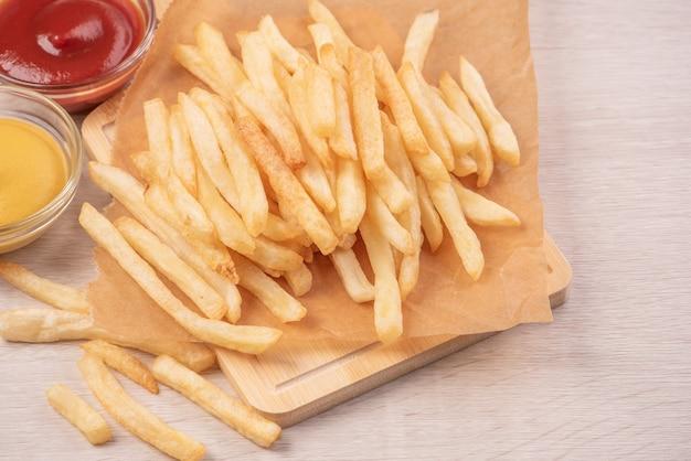 Deliciosas papas fritas doradas sobre papel kraft para hornear y bandeja para comer con salsa de tomate y mostaza amarilla, cerca, estilo de vida.