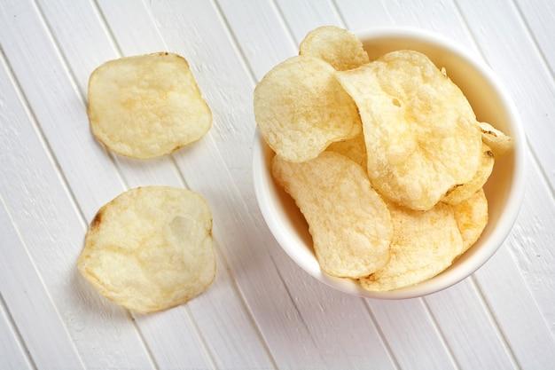 Deliciosas papas fritas de oro en un recipiente blanco sobre un fondo blanco de madera.