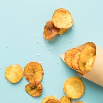 Deliciosas papas fritas sobre fondo azul.