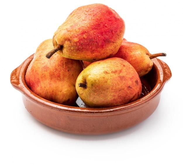 Deliciosas peras rojas en cazuela de barro. aislado.