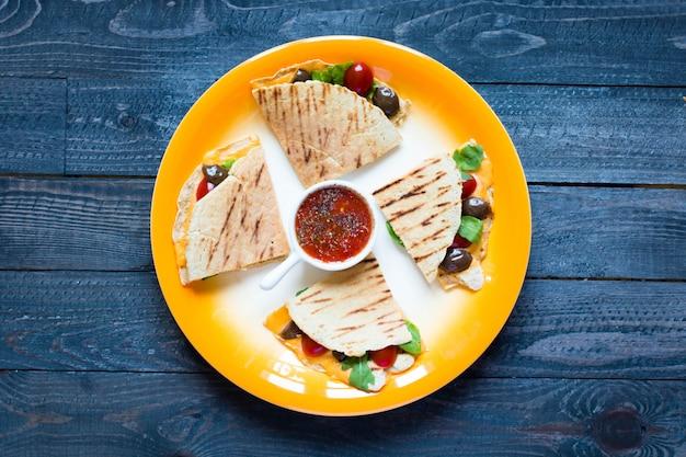 Deliciosas quesadillas vegetarianas con tomate, aceitunas, salada y queso cheddar