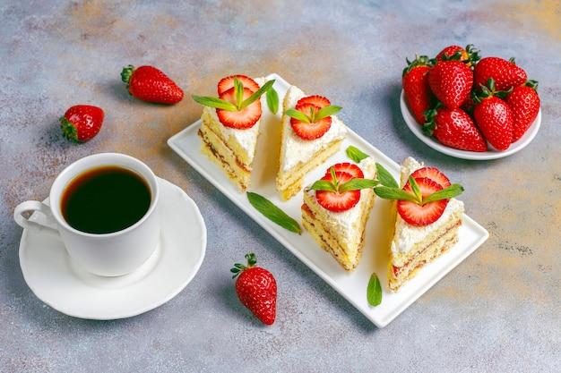 Deliciosas rebanadas caseras de tarta de fresas con crema y fresas frescas
