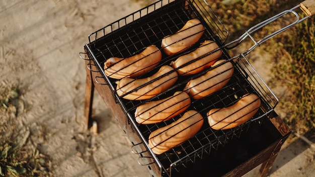 Deliciosas salchichas asadas descansando sobre la rejilla de hierro de una barbacoa portátil sobre brasas mientras se cocinan a la perfección