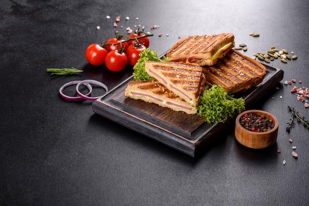 Deliciosas tostadas frescas a la parrilla con queso y jamón. sándwiches, refrigerio rápido