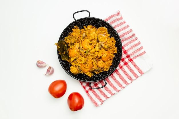 Delicioso arroz español en una paellera sobre fondo blanco.