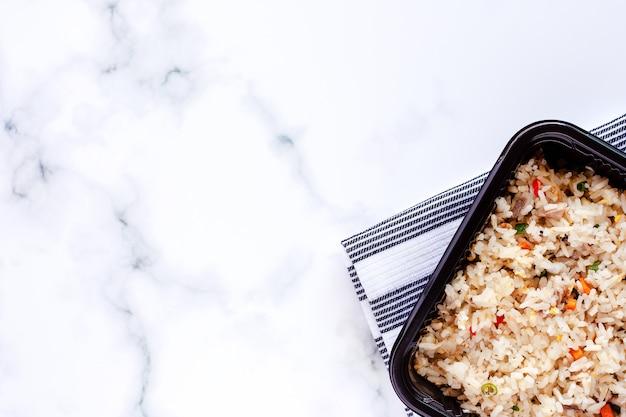 Delicioso arroz frito en lonchera con servilleta sobre fondo de mármol