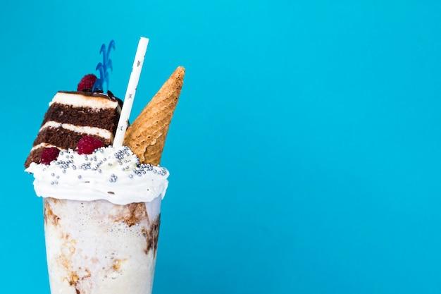 Delicioso batido con helado y pastel sobre fondo azul.