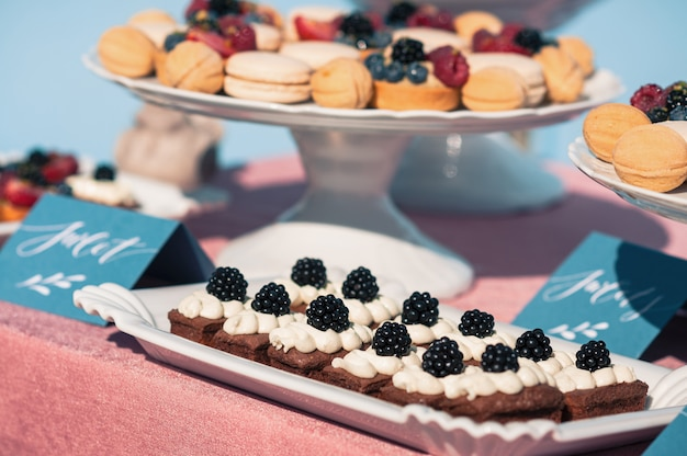 Delicioso buffet dulce con cupcakes, macarrones y otros postres.