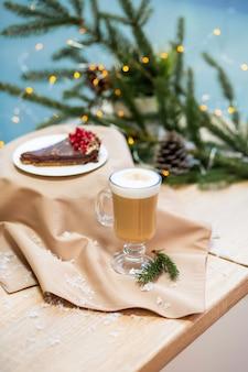 Delicioso café capuchino festivo fresco de la mañana en una taza de vidrio y postre de cupcake en la mesa de madera, luciérnagas y ramas de abeto