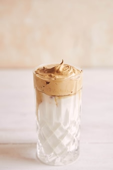 Delicioso café dalgona fresco de moda con leche en una mesa de madera blanca