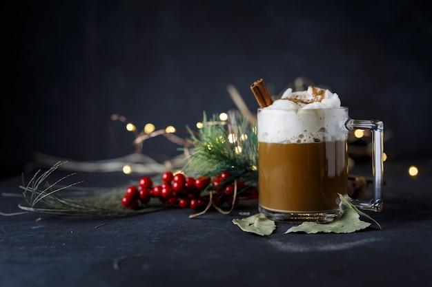 Delicioso café navideño con canela y espuma, junto a acebos sobre una superficie oscura