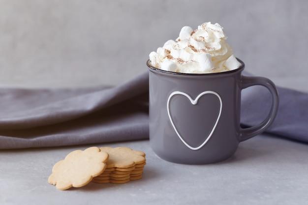 Delicioso chocolate caliente con crema batida y galletas sobre fondo de piedra gris. copia espacio