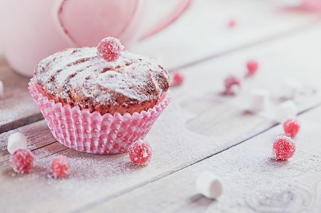 Delicioso cupcake con bayas y una taza de café.
