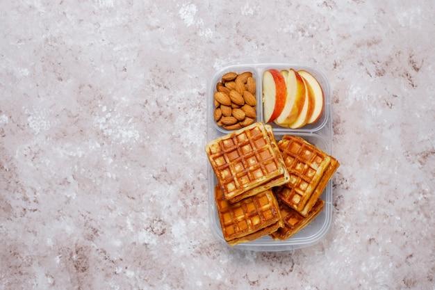 Delicioso desayuno con almendras, rodajas de manzana roja, gofres, cruasanes en una lonchera de plástico a la luz