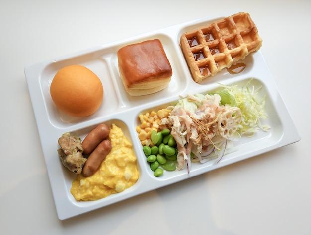 Delicioso desayuno buena mañana en bandeja de comida en la mesa blanca.