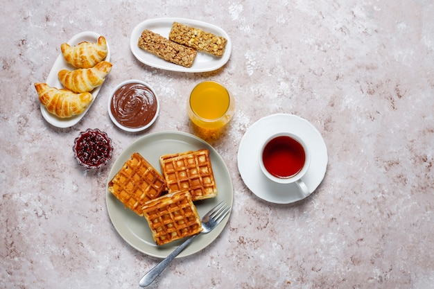 Delicioso desayuno con café, jugo de naranja, gofres, cruasanes, mermelada, pasta de nueces a la luz, vista superior