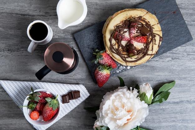 Delicioso desayuno con café, panqueques con fresas y chocolate en la mesa
