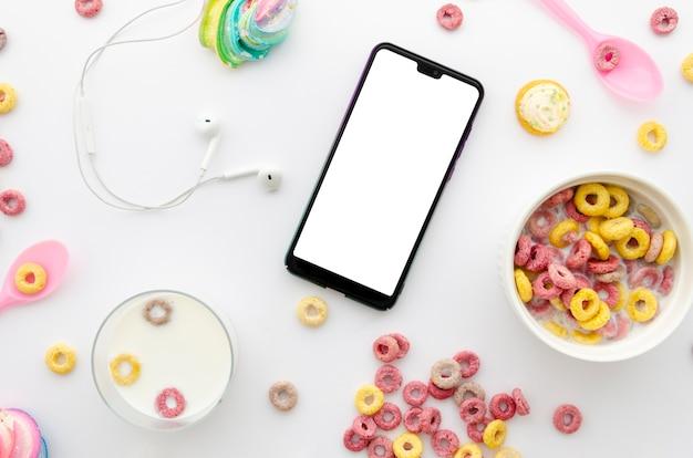 Delicioso desayuno con cereales y teléfono móvil en la mesa