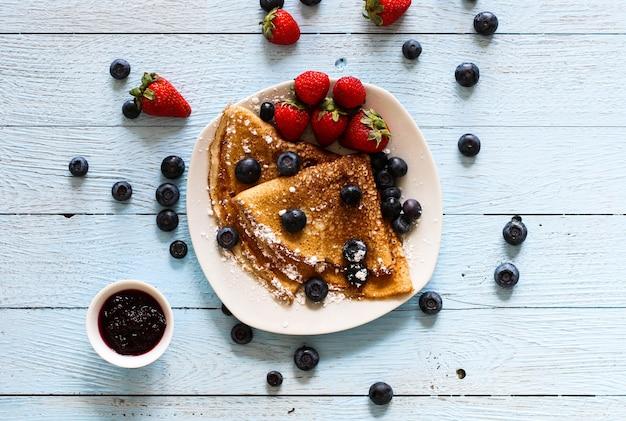 Delicioso desayuno de crepes con dramática madera clara