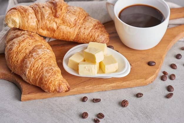 Delicioso desayuno con croissants recién hechos y café servido con mantequilla.