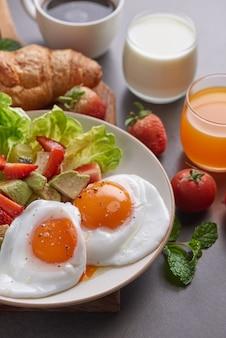 Delicioso desayuno con cruasanes recién hechos y café servido, leche, jugo de naranja.