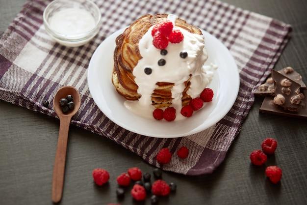 Delicioso desayuno para la familia, pancacks con crema agria y bayas, mesa de cocina decorada con frambuesas, arándanos, cuchara de madera