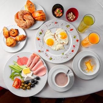Delicioso desayuno en una mesa con ensalada, huevos fritos y pastelería vista superior sobre un fondo blanco.