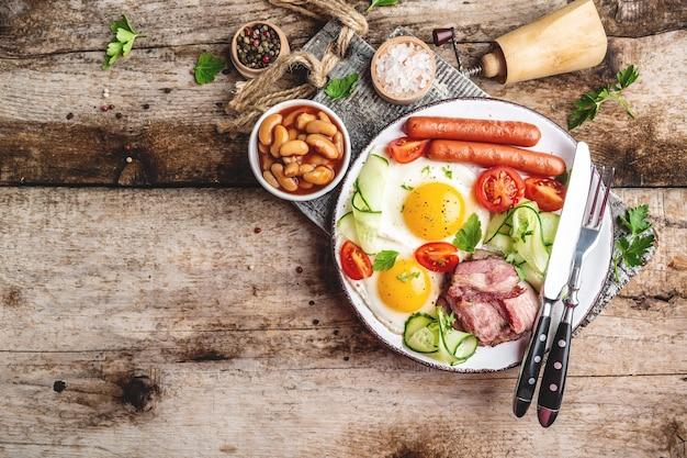Delicioso desayuno o almuerzo con huevos fritos, frijoles, tomates, tocino en la mesa de madera, vista superior.