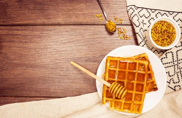 Delicioso gofre belga con miel y polen de abeja en escritorio de madera