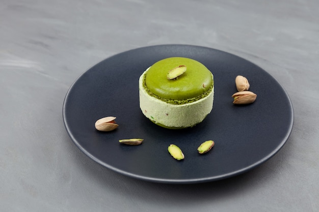 Delicioso helado de pistacho con macarons de pistacho o macarrones en un plato oscuro.