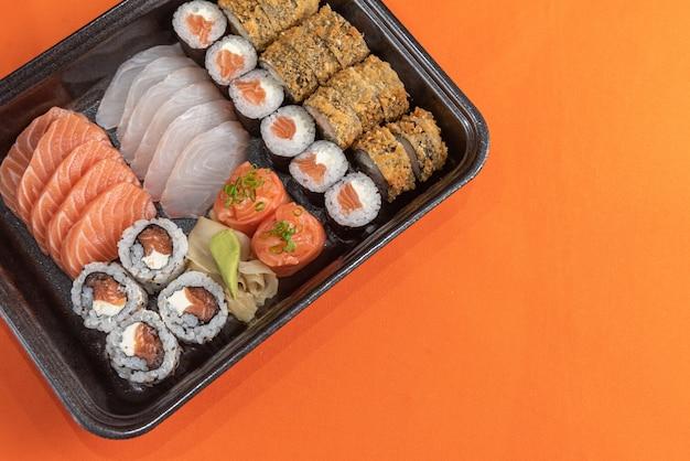 Delicioso y hermoso sushi en la mesa naranja